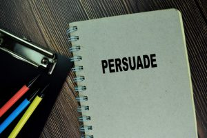 notebook with word 'persuade' on cover